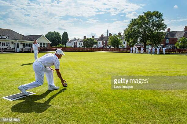 Men playing bowls on a village bowling green