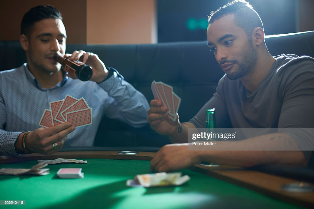 Men playing card game for cash at pub card table