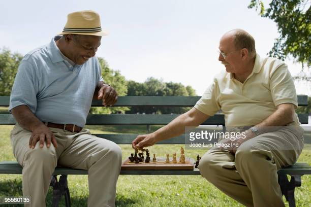 Men playing chess on park bench