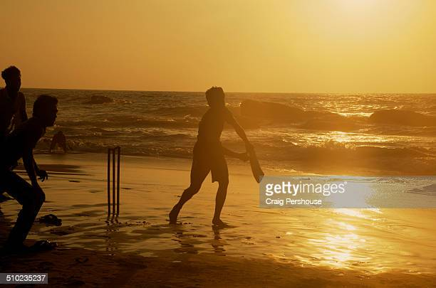 Men playing cricket on the beach at sunset