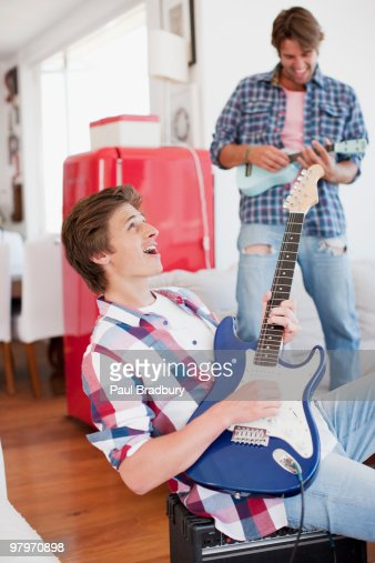Men playing electric guitar and ukulele : Stock Photo