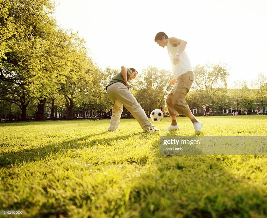 2 Men playing Football in Park : Stock Photo