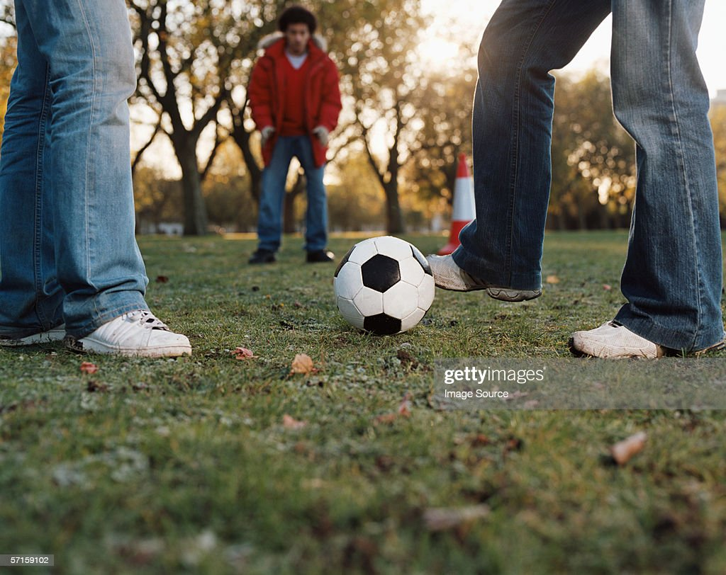 Men playing football in park : Stock Photo