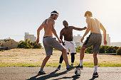 Three men playing football on a sunny day. Men practicing football tackling skills.