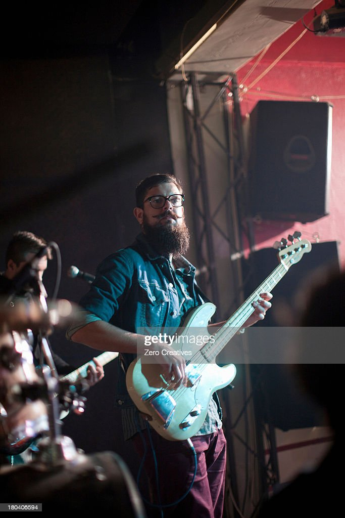 Men playing guitars on stage in club