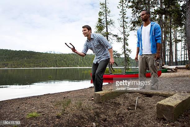 Men playing horseshoes.