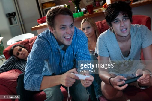 men playing on computer game, women bored : Stock Photo