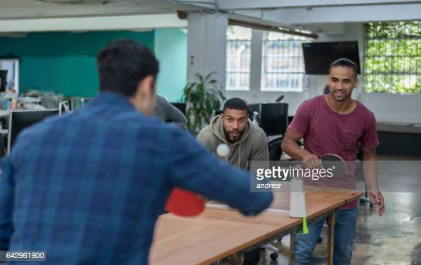 Men playing ping-pong at the office