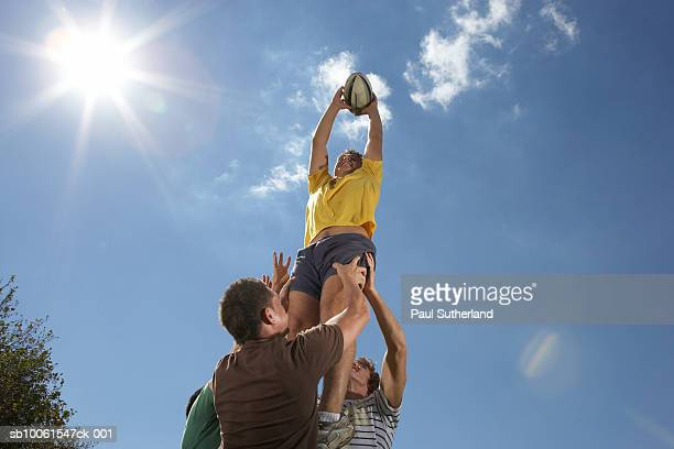 Men playing rugby, holding man with ball up in air, low angle view