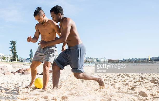 Men playing soccer at the beach