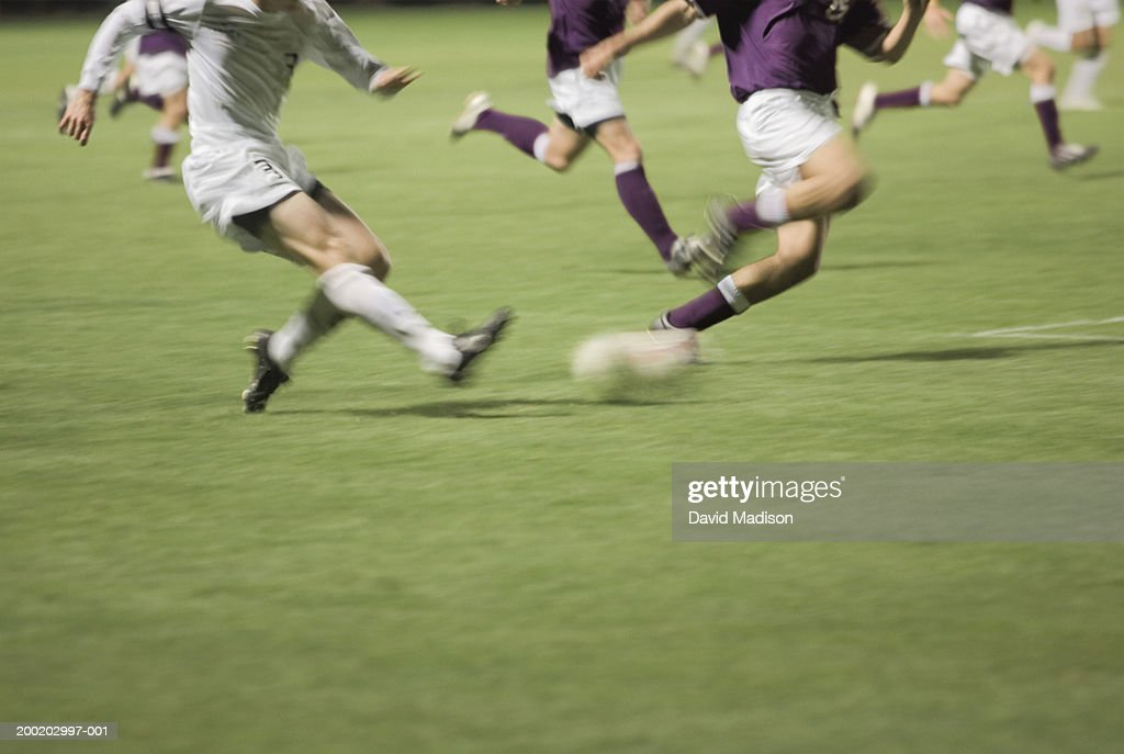 Men playing soccer, low section (blurred motion) : Stock Photo