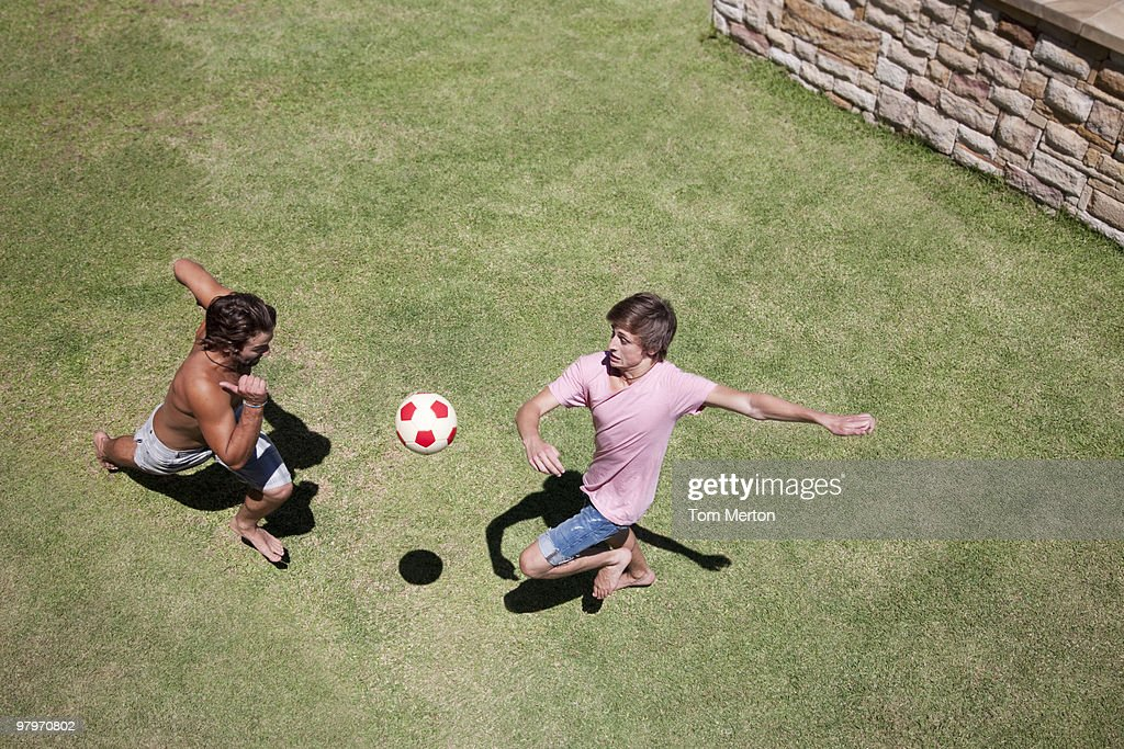 Men playing soccer on grass : Stock Photo