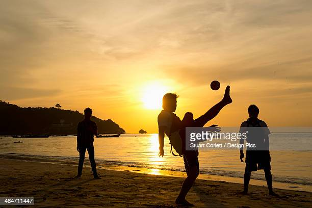 Men playing takraw ball at sunset on the beach