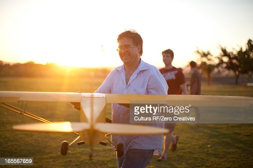 Men playing with toy airplane in park