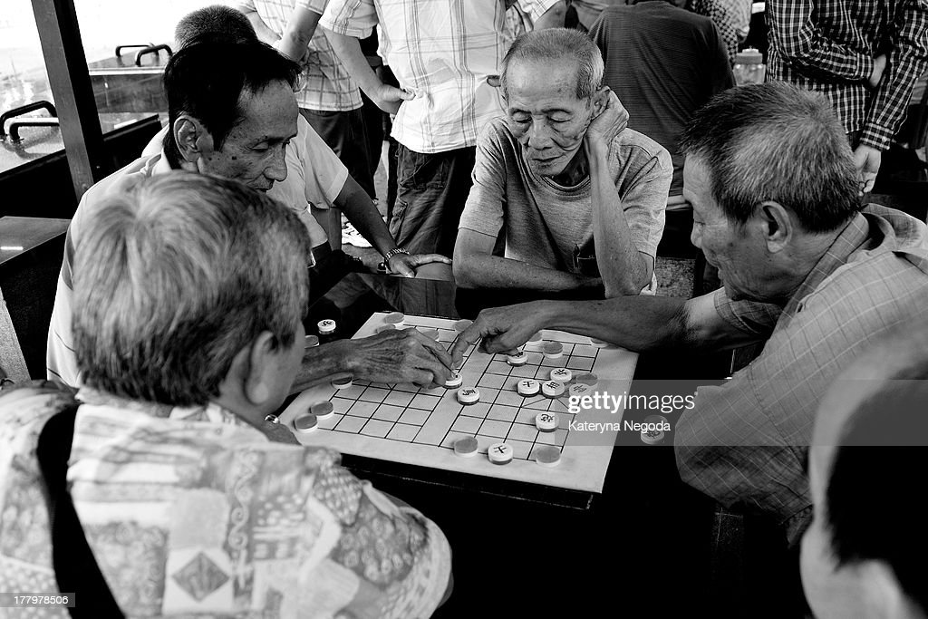 CONTENT] Men playing Xiangqi (Chinese Chess)outside in China Town, Singapore. A xiangqi gameboard and pieces on the table.Black and White.