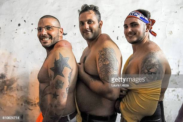 Men pose for a photo just after the annual Festa dei Gigli with their shoulder strain called 'patana' or 'pataniello' caused by having carried a...