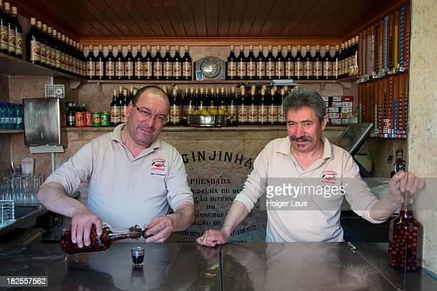 Men pour cherry liquor at Ginjinha Espinheira bar