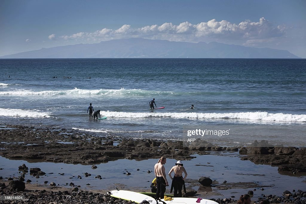Men practice surf at the beach of Las Americas on the Spanish Canary Island of Tenerife on December 11, 2012.