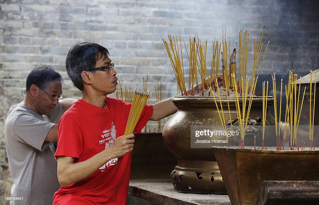 Men pray and place incense at Pak Tai Temple, on the first day of the Cheung Chau Bun Festival on May 14, 2013 in Hong Kong, Hong Kong. Today is the start of the Cheung Chau Bun Festival which will run until 17 May and celebrates the eight day of the fourth moon in the Chinese calendar.