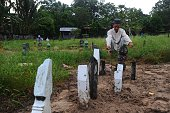 Men pray for relatives at a cemetery on the first day of Eid alFitr celebrations in Thailand's southern province of Narathiwat on July 6 2016 Muslims...