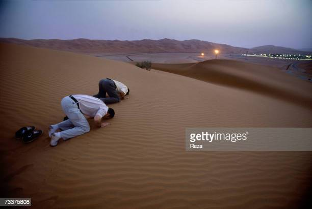 Men pray in the dunes just outside the Saudi Aramco oil field complex facilities at Shaybah in the Rub' al Khali desert on March 2003 in Shaybah...