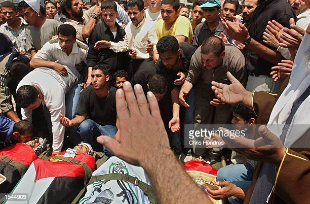 Men pray over bodies at a funeral for four Palestinian militants May 23 2002 in the West Bank town of Nablus The militants were allegedly killed by...