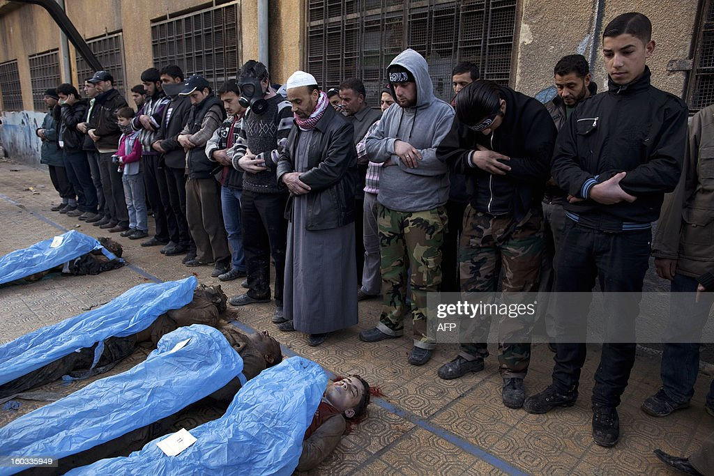 Men pray over the bodies of Syrian civilians executed and dumped in the Quweiq river, in the grounds of the courtyard of a Yarmouk School, in the Bustan al-Qasr district of Aleppo, on January 29, 2013. The bodies of at least 65 young men, all executed with a single gunshot to the head or neck, were found in a river in Aleppo city, adding to the grim list of massacres committed during Syria's 22-month conflict. AFP PHOTO/JM LOPEZ