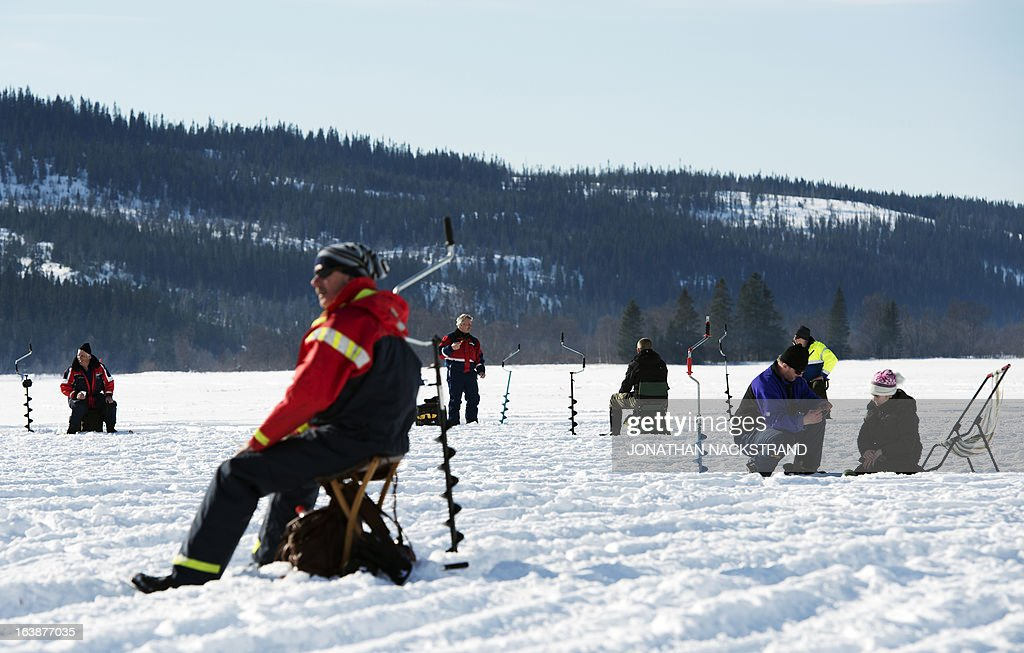 Men prepare their fishing poles and drills as they participate in an ice fishing contest on the frozen Oster-Jansjon lake in Are, Sweden on March 17, 2013.