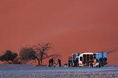 Men preparing breakfast under a giant sand dune