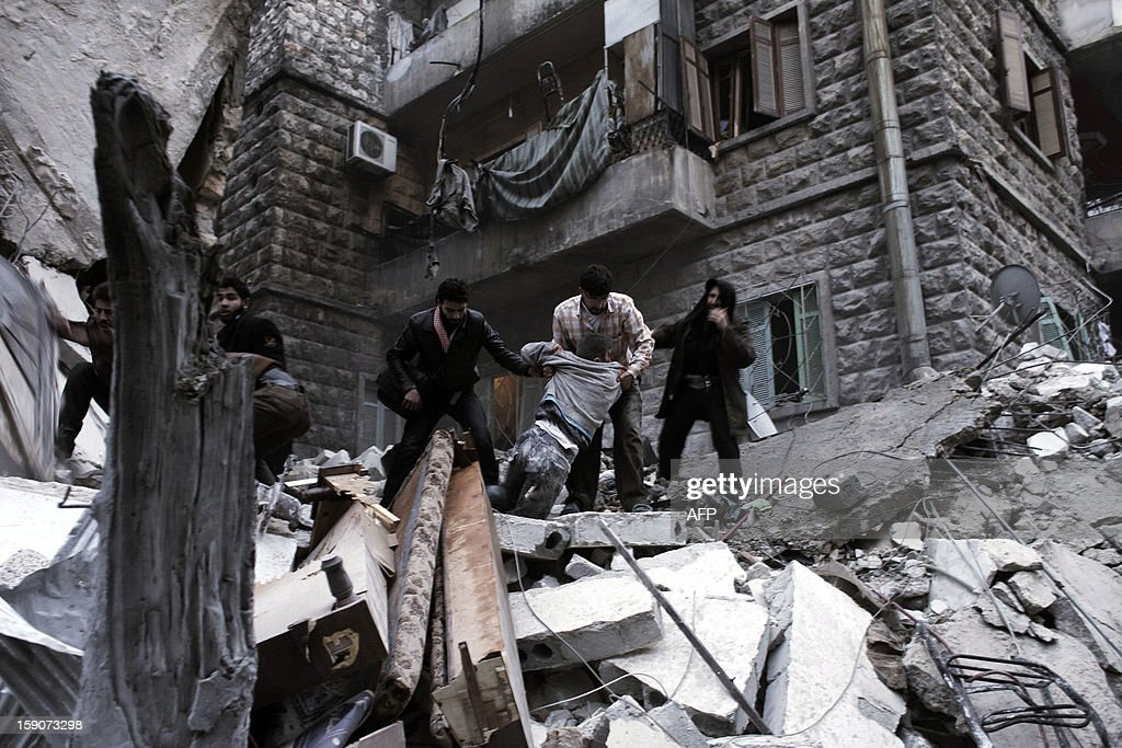 Men pull the body of a wounded person from the rubble of a building targeted by a missile in the al-Mashhad neighbourhood of Aleppo on January 7, 2013. The United Nations recently denounced a 'proliferation of serious crimes including war crimes' in Syria, as ever more horrifying images and videos emerge from the country. AFP PHOTO / ACHILLEAS ZAVALLIS