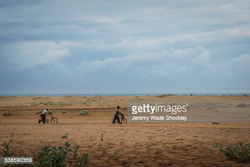 Men pushing bicycles across beach in South Africa.