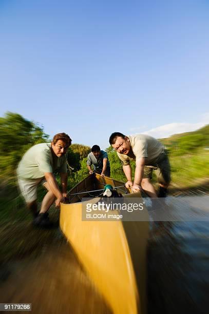 Men pushing boat into water