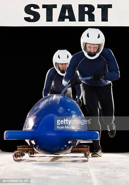 Men pushing bobsleigh, portrait