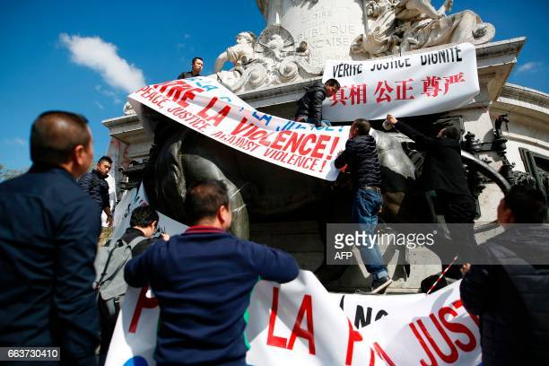 Men put banners on the statue of the Republic representing Marianne as they take part in a rally on the Place de la Republique in Paris on April 2...