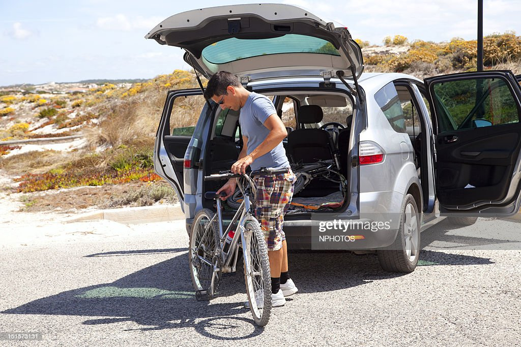 Men putting bicycles in car : Stock Photo