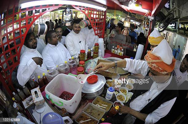 Men queue at a take away stand in the Saudi Red Sea port of Jeddah in the early hours of August 26 as practicing Muslims eat their light 'suhur' meal...