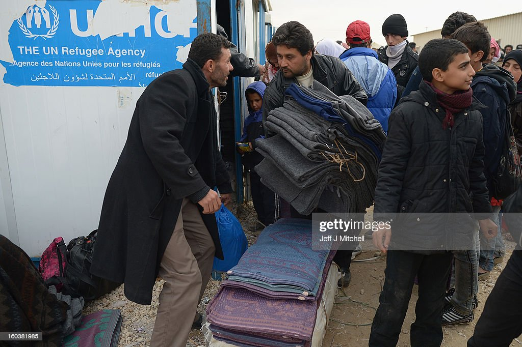 ZA'ATARI, JORDAN - JANUARY 30: Men queue for blankets as new Syrian refugees arrive at the International Organization for Migration at the Za'atari refugee camp on January 30, 2013 in Mafrq, Jordan. Record numbers of refugees are fleeing the violence and bombings in Syria to cross the borders to safety in northern Jordan and overwhelming the Za'atari camp. The Jordanian government are appealing for help with the influx of refugees as they struggle to cope with the sheer numbers arriving in the country.