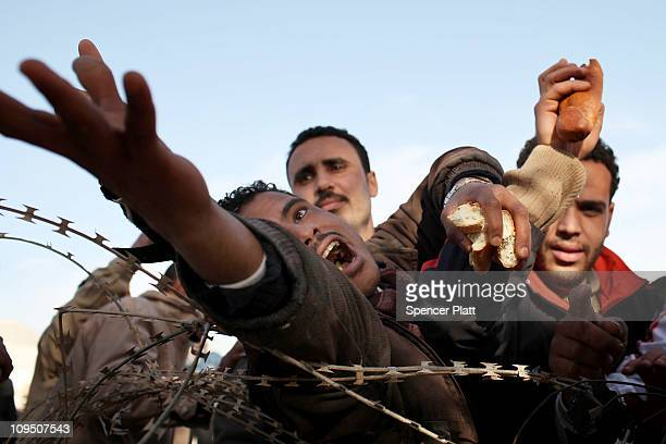 Men reach for bread behind barbed wire while waiting to enter Tunisia after fleeing Libya on February 28 2011 in Ras Jdir Tunisia As fighting...