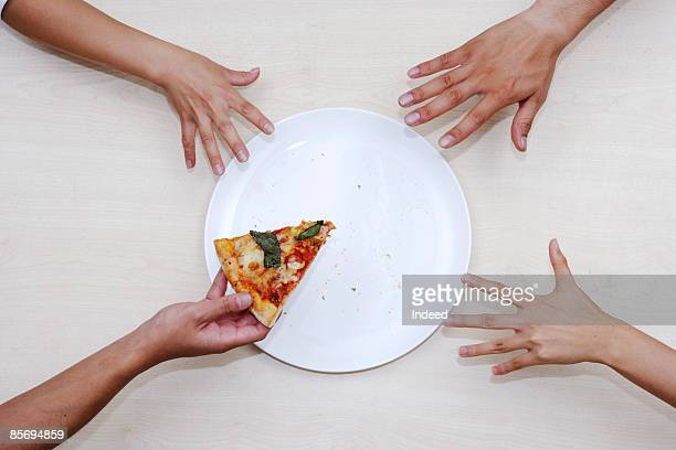 Men reaching last pizza from plate