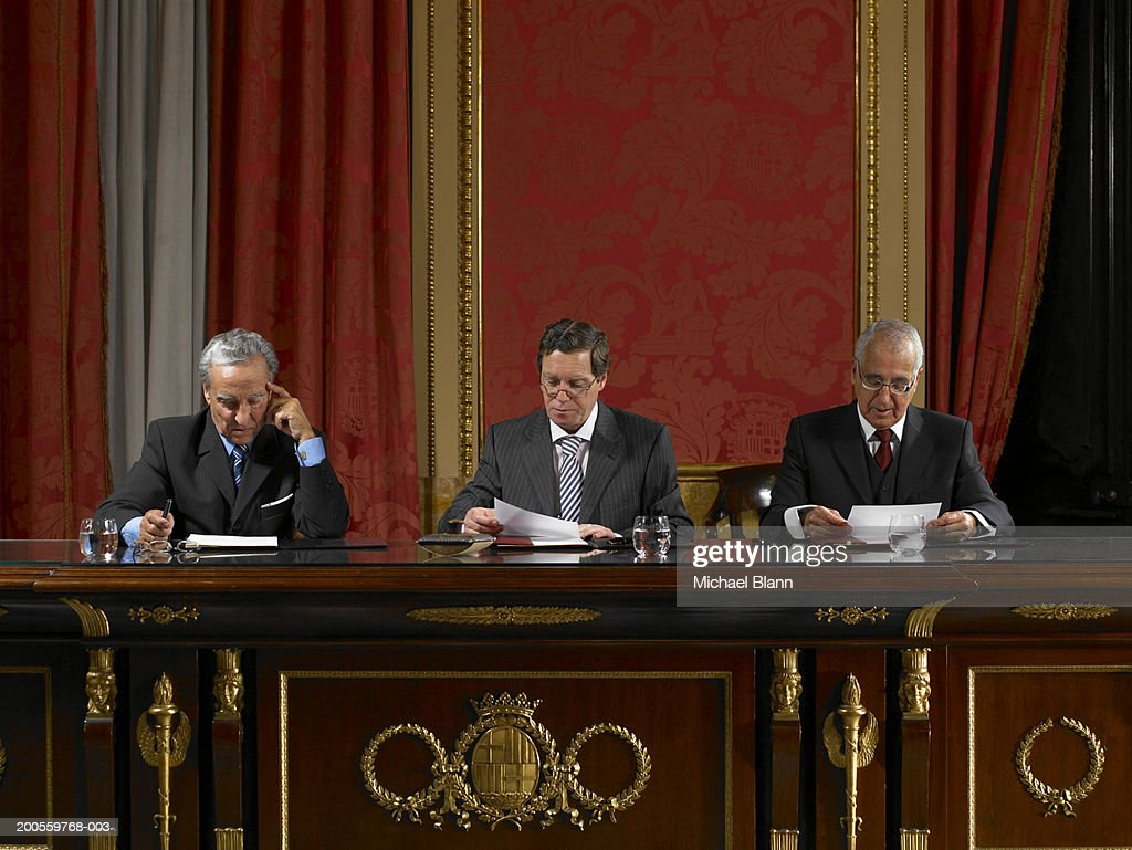 Men reading document at conference table : Stock Photo