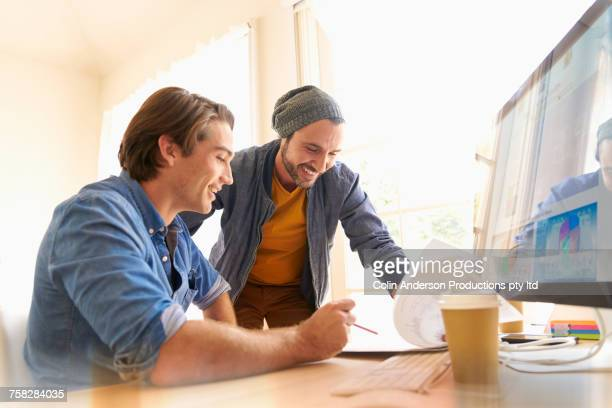 Men reading paperwork near computer in office