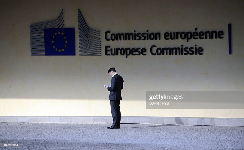 A men reads documents on February 20, 2013 outside the European Commission Berlaymont building at the EU Headquarters in Brussels. AFP PHOTO/JOHN THYS