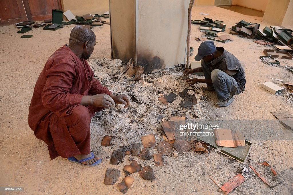 Men recover burnt ancient manuscripts at the Ahmed Baba Centre for Documentation and Research in Timbuktu on January 29, 2013. French-led forces seized yesterday Mali's fabled desert city of Timbuktu in a lightning advance north as fleeing Islamists torched a building housing priceless ancient manuscripts. Mayor Ousmane confirmed the fire at the Ahmed Baba Centre for Documentation and Research which housed between 60,000 and 100,000 manuscripts, according to Mali's culture ministry. AFP PHOTO / ERIC FEFERBERG