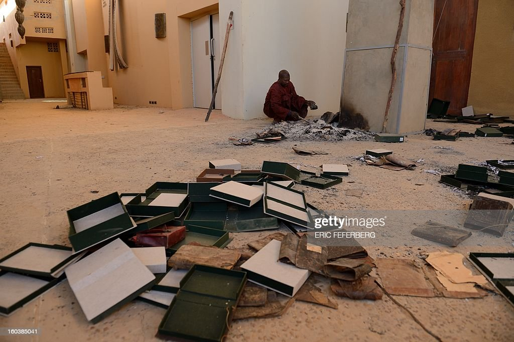 Men recover burnt ancient manuscripts at the Ahmed Baba Centre for Documentation and Research in Timbuktu on January 29, 2013. French-led forces seized yesterday Mali's fabled desert city of Timbuktu in a lightning advance north as fleeing Islamists torched a building housing priceless ancient manuscripts. Mayor Ousmane confirmed the fire at the Ahmed Baba Centre for Documentation and Research which housed between 60,000 and 100,000 manuscripts, according to Mali's culture ministry.