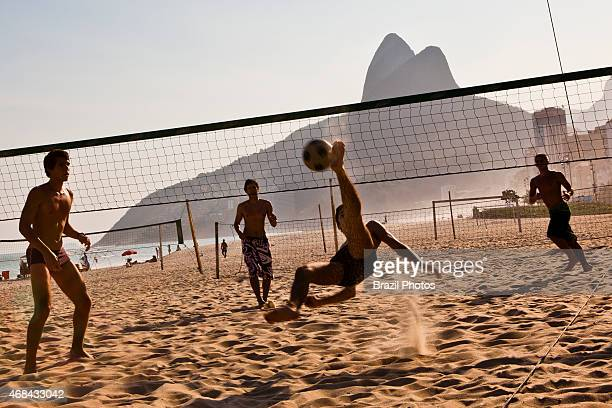 Men recreating at Ipanema beach play futevolei a beach volleyball game played on the beach using only feet chest and head to hit the ball Rio de...