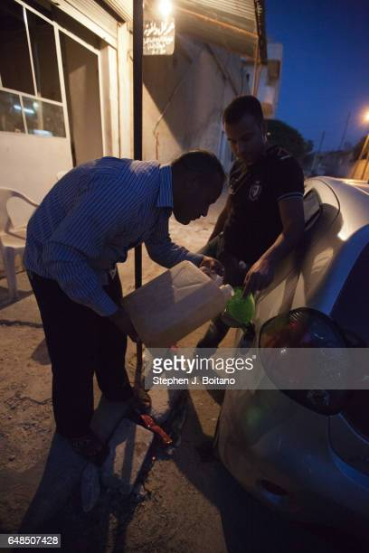 A'ZAZ ALEPPO SYRIA Men refuel a car from plastic jugs of gasoline in Azaz Syria