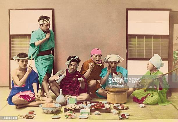 Men relax while eating and being serenaded by one member playing a stringed instruent like a guitar