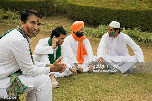 Men relaxing during Holi celebration