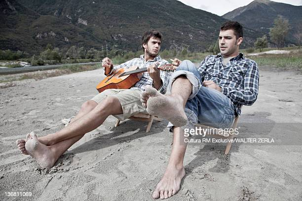 Men relaxing in lawn chairs by lake