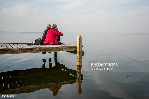 Men Relaxing On Jetty At Lake Steinhude Meer Against Sky